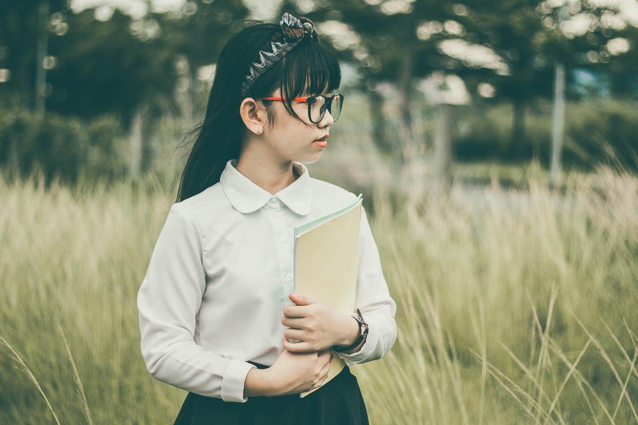 赤い眼鏡をかけた女子中学生がノートを持っている写真