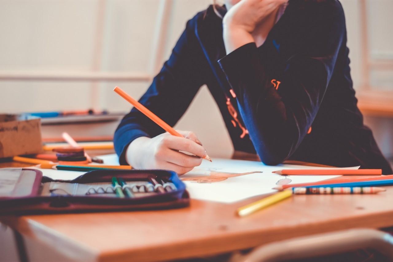 小学生が机のノートにメモをとる写真